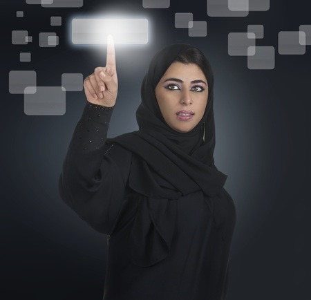 gulf: arabian businesswoman pressing a touchscreen button with hijab  Stock Photo