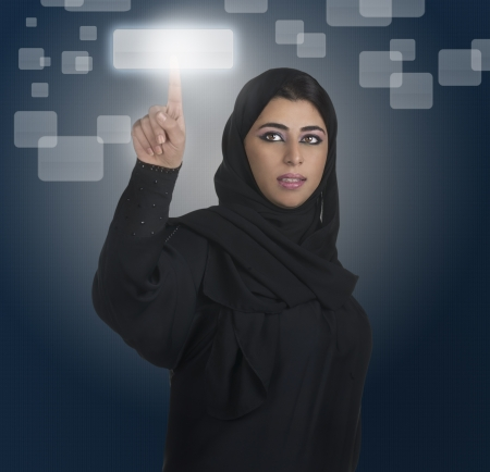 the gulf: arabian businesswoman pressing a touchscreen button with hijab  Stock Photo