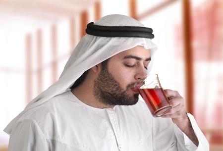 arabian guy drinking tea against a nice moody background  photo