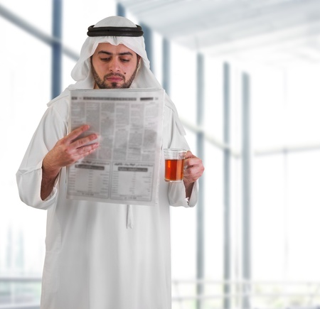 arabian business man in office drinking tea   reading news  photo