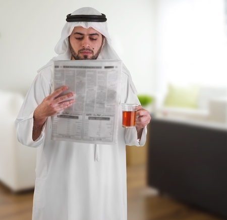 arabian business man at home drinking tea   reading news  photo
