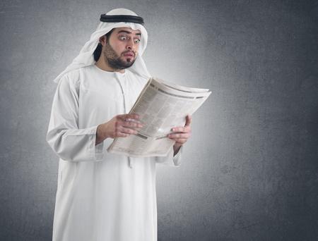 banking problems: arabian businessman shocked while reading newspaper  Stock Photo