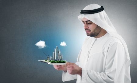 ksa: arabian businessman with a virtual city presentation on a pad