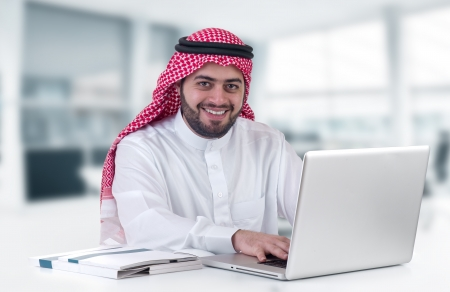 arabian businessman using laptop in his office
