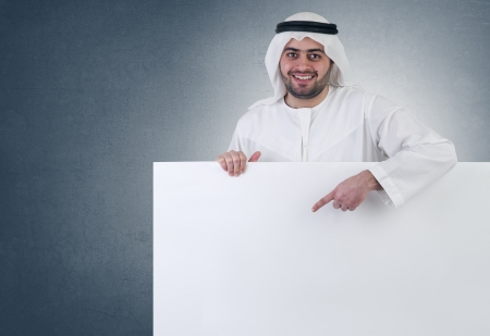 arab people: arabian business man pointing at a blank white sign  Stock Photo