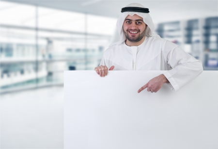 arab adult: arabian business man pointing at a blank white sign  Stock Photo