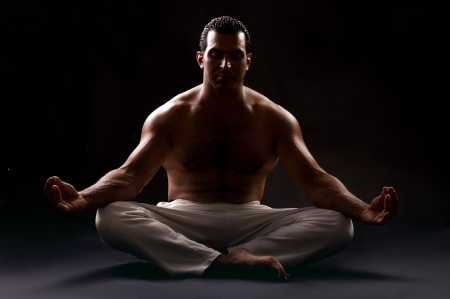 Bare chested guy Practicing yoga in low key shot  Stock Photo - 14683414