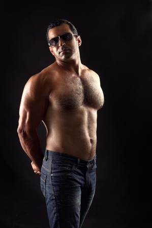 portrait of topless athletic man posing over black background  photo