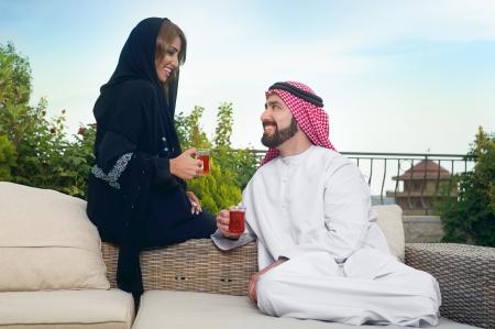 the emirates: Pareja �rabe se relaja en el jard�n y beber t� Foto de archivo