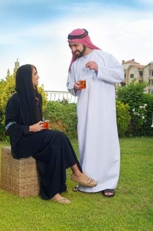 Arabian couple relaxing in the garden and drinking tea Imagens - 16466691