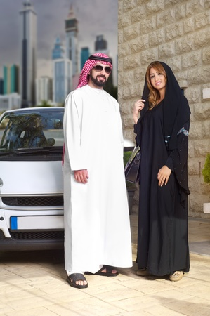 arabian couple against their car posing at home with cityscape behind photo