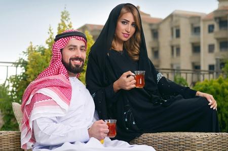 arabian: Arabian couple relaxing in the garden and drinking tea