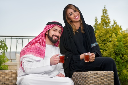 bahrain: Arabian couple relaxing in the garden and drinking tea