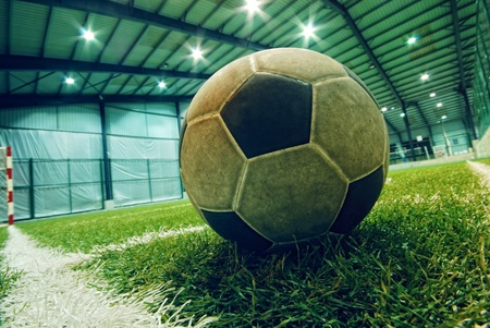 indoor soccer: soccer ball on green grass in an indoor playground