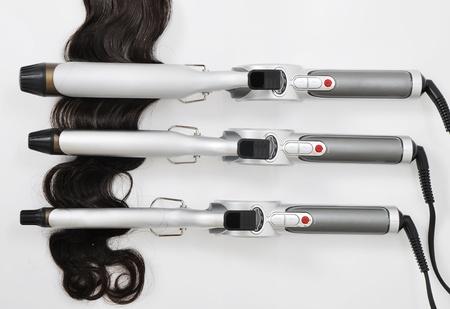 peluqueria: rizar el cabello de hierro con la extensión del pelo Foto de archivo