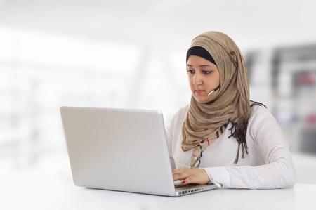 Arabian Customer Representative with headset working on laptop