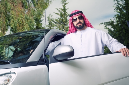 arabian guy posing against his car at home photo