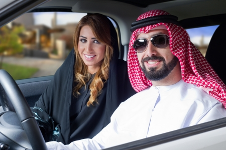 purchased: arabian couple in a newely purchased car enjoying life