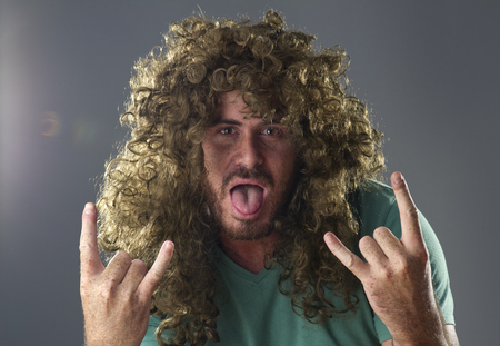 metal music: Portrait of a guy with a wig doing a rock and roll symbol