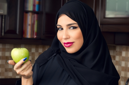 Arabian woman holding an apple in the kitchen   Stock Photo