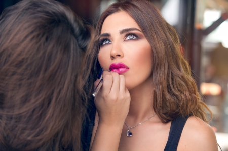 Professional makeup artist applying make up on a beautiful young model s face