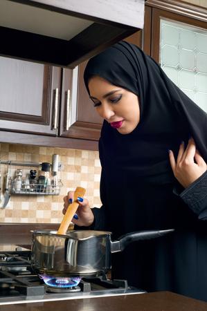 arabian food: Arabian woman stirring food in the casserole