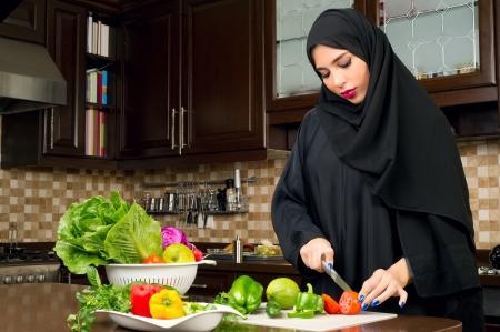 girl with knife: Arabian woman wearing hijab cutting veggies in the kitchen