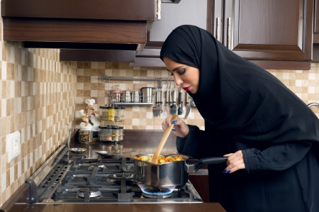 Arabian woman cooking stew in the kitchen   Imagens