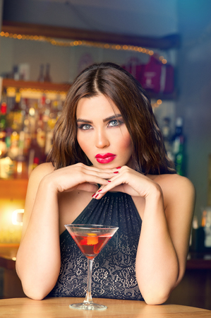 Sexy young woman with a glass of martini in a pub   photo
