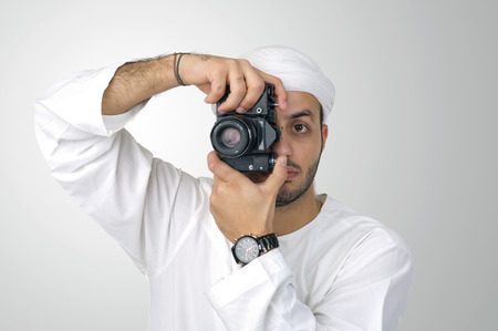 Young Arabian man using holding his camera ready to shoot, isolated photo