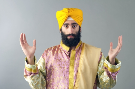 Portrait of Indian sikh man with his hands raised photo