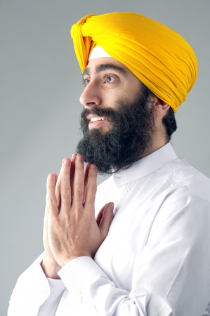 Portrait of Indian sikh man with a bushy beard praying photo