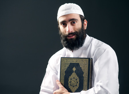 quran: arabian muslim man with beard holding the holy book Quran Stock Photo