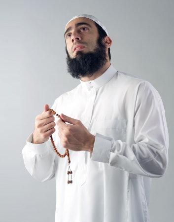 Arabian muslim man holding rosemary and praying photo