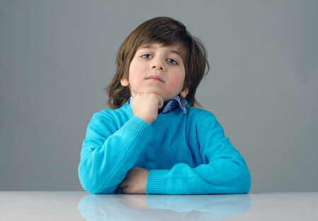 beautiful kid with deep thoughts thinking isolated against grey background photo