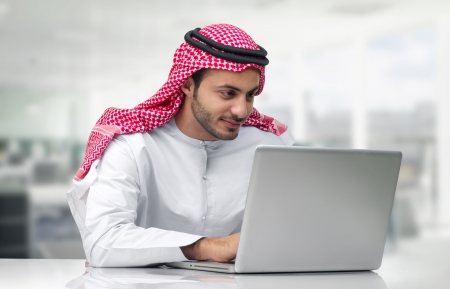 彼の事務所でノート パソコンで作業するアラビアン ビジネス男性