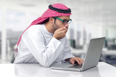 Arabian business man looking shocked at his computer photo