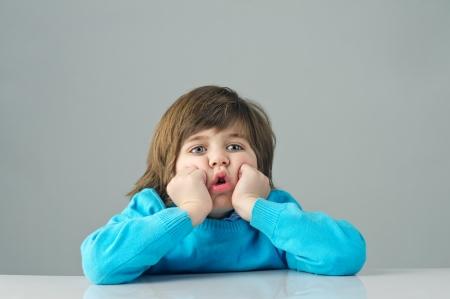 beautiful kid feeling bored isolated on grey background Standard-Bild