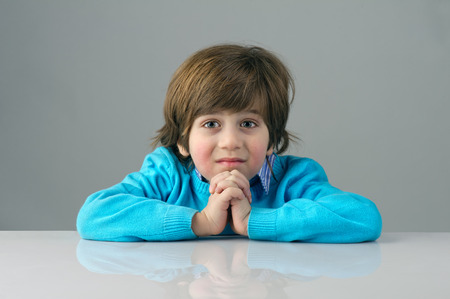 beautiful kid feeling bored isolated on grey background photo