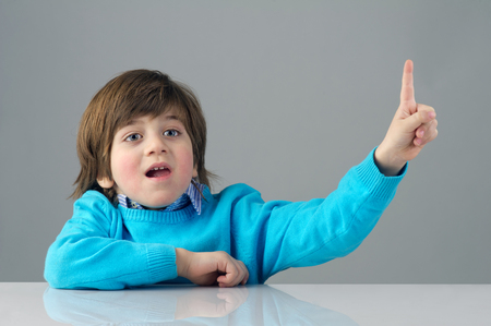 child finger: Portrait of a beautiful child raising his finger