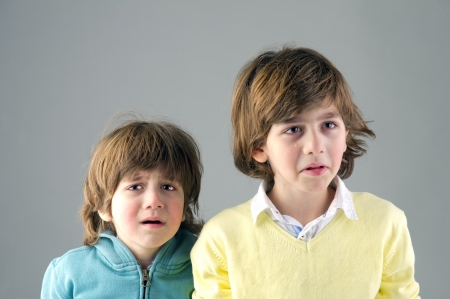 Studio portrait of two young brothers feeling worried photo