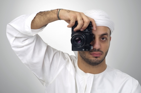 abudhabi: Young Arabian man using holding his camera ready to shoot, isolated Stock Photo