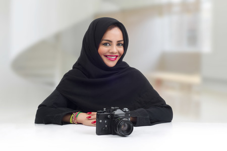 Ambitious Arabian photographer posing with her professional camera photo
