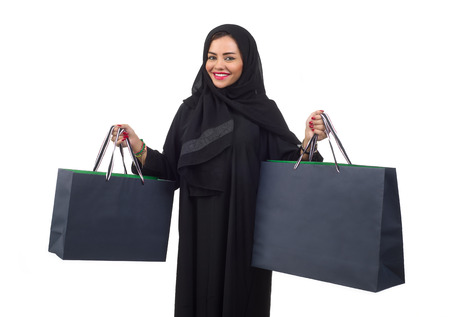 saudi: Arabian woman carrying shopping bags isolated on white Stock Photo