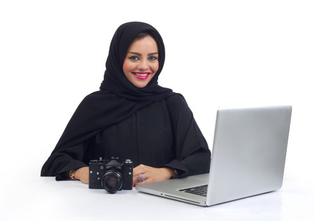 abudhabi: Arabian photographer working on her Laptop at the office