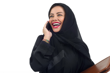 abudhabi: Arabian business woman holding a folder and talking on the phone isolated on white