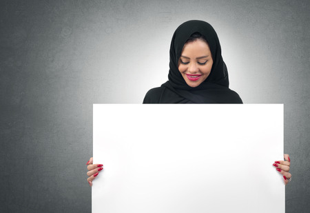 KSA: Arabian business woman holding a white board isolated Stock Photo