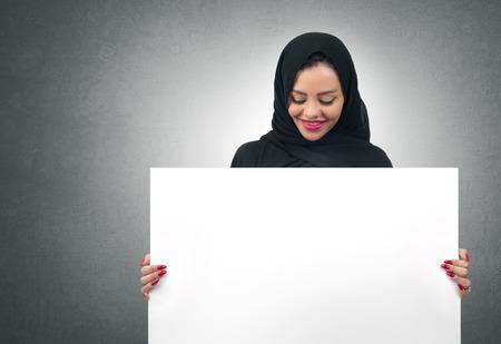femmes muslim: Arabian femme d'affaires tenant un tableau blanc isol� Banque d'images