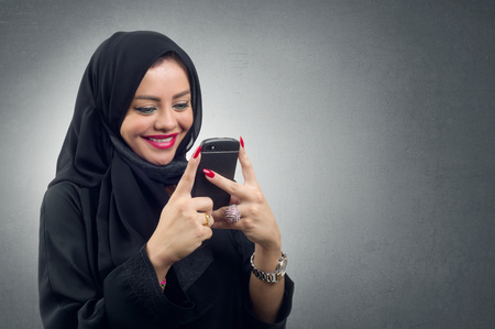 Arabian lady wearing hijab using her mobile isolated photo
