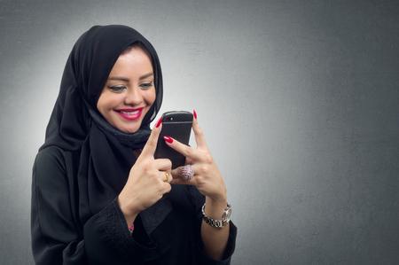 arab hijab: Arabian lady wearing hijab using her mobile isolated